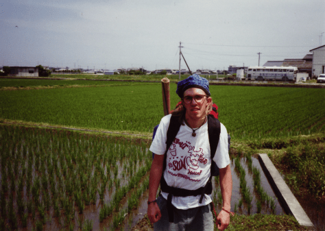 Japan hitch-hiking: sometimes ya gotta wander a ways to find a place which has traffic coming by and a place to pull over. hot and humid no doubt as stroll past wet-field rice paddies