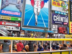 A boat-full of tourists going nuts over Glico Man