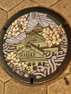 Osaka sewer manhole, featuring Osaka Castle. Every city in Japan has unique manhole cover designs. This one's pretty nice, eh?