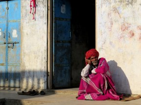 Old man sits by the door, India