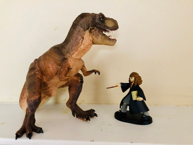 Picture shows a T. rex facing off Hermione Granger