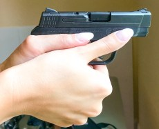 Support side view of two-handed grip on small pistol by large left-handed shooter