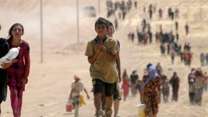 Children from the minority Yazidi sect, fleeing violence from forces loyal to the Islamic State in Sinjar town, make their way towards the Syrian border, on the outskirts of Sinjar mountain, near the Syrian border town of Elierbeh of Al-Hasakah Governorate August 10, 2014. Islamic State militants have killed at least 500 members of Iraq's Yazidi ethnic minority during their offensive in the north, Iraq's human rights minister told Reuters on Sunday. The Islamic State, which has declared a caliphate in parts of Iraq and Syria, has prompted tens of thousands of Yazidis and Christians to flee for their lives during their push to within a 30-minute drive of the Kurdish regional capital Arbil.  Picture taken August 10, 2014. REUTERS/Rodi Said (IRAQ - Tags: POLITICS CIVIL UNREST CONFLICT)