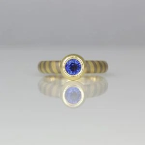 Sapphire rub-over set in yellow gold on diagonal stripe ring