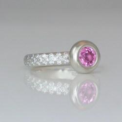 Pink sapphire on diamond set platinum ring