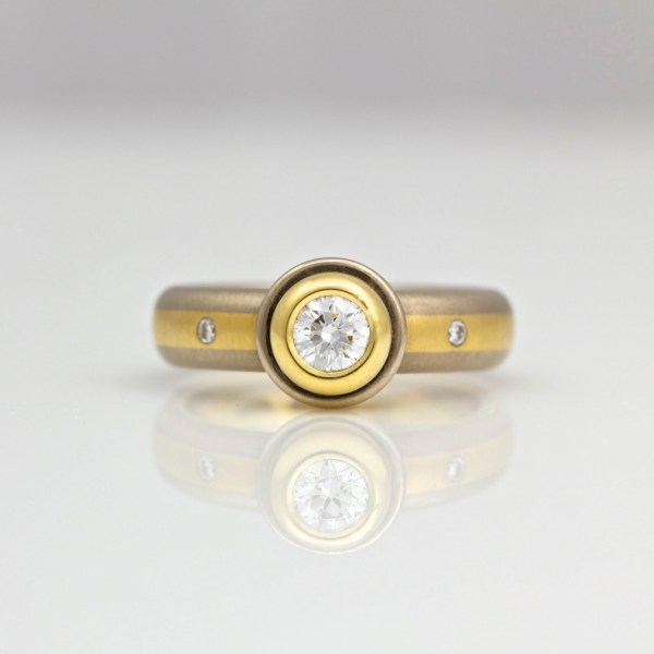 Diamond rub-over set in yellow gold on center stripe ring