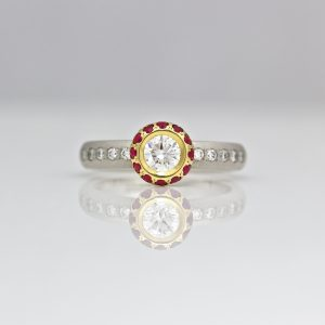 Diamond framed with rubies on a diamond set platinum ring