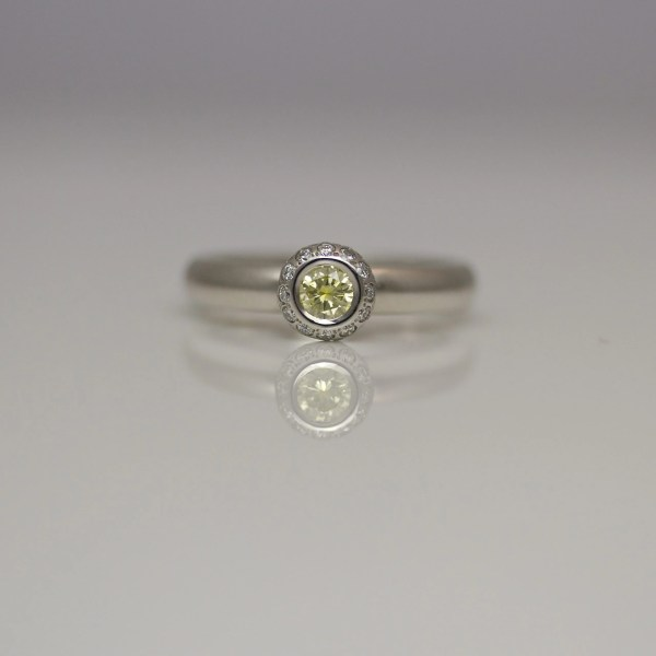 Natural yellow diamond, rub-over set in platinum with white diamond halo