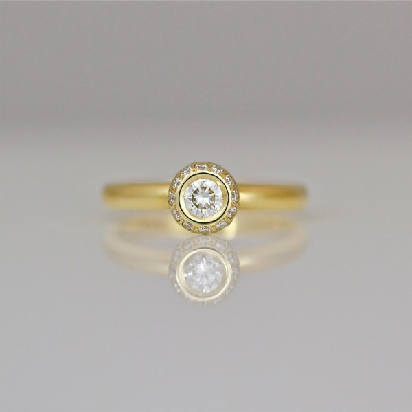 Diamond rub-over set in yellow gold ring with diamond halo. 0950