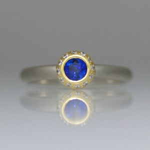 Sapphire rub-over set with diamond halo ring