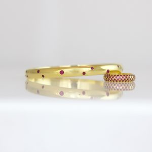 Rubies flush set in 18ct yellow gold bangle