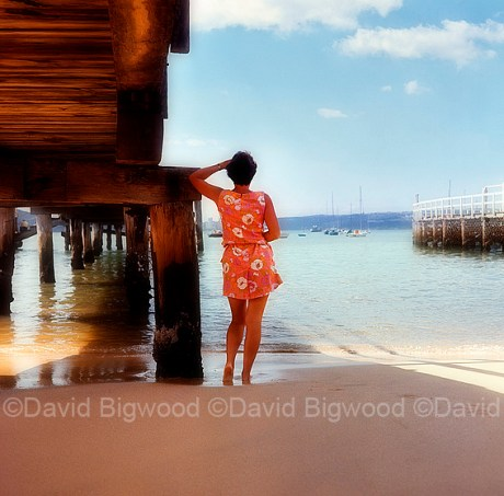 Lady watching boats from beach