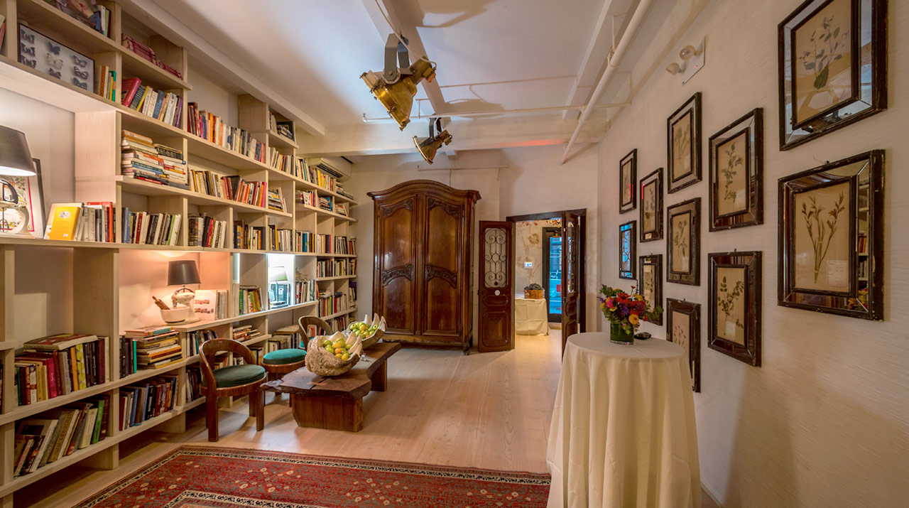Chef David Bouley's Library. Heavy spotlights on the ceiling illuminate a bookshelf of cookbooks, floor to ceiling, running down the left side of the room. A Persian carpet, a giant clamshell full of apples, pictures of herbs and a heavy wooden armoire complete the decor.