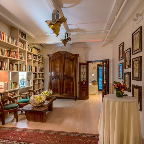 A bookshelf of cookbooks, floor to ceiling, a Persian carpet, a giant clamshell full of apples, pictures of herbs and a heavy wooden armoire