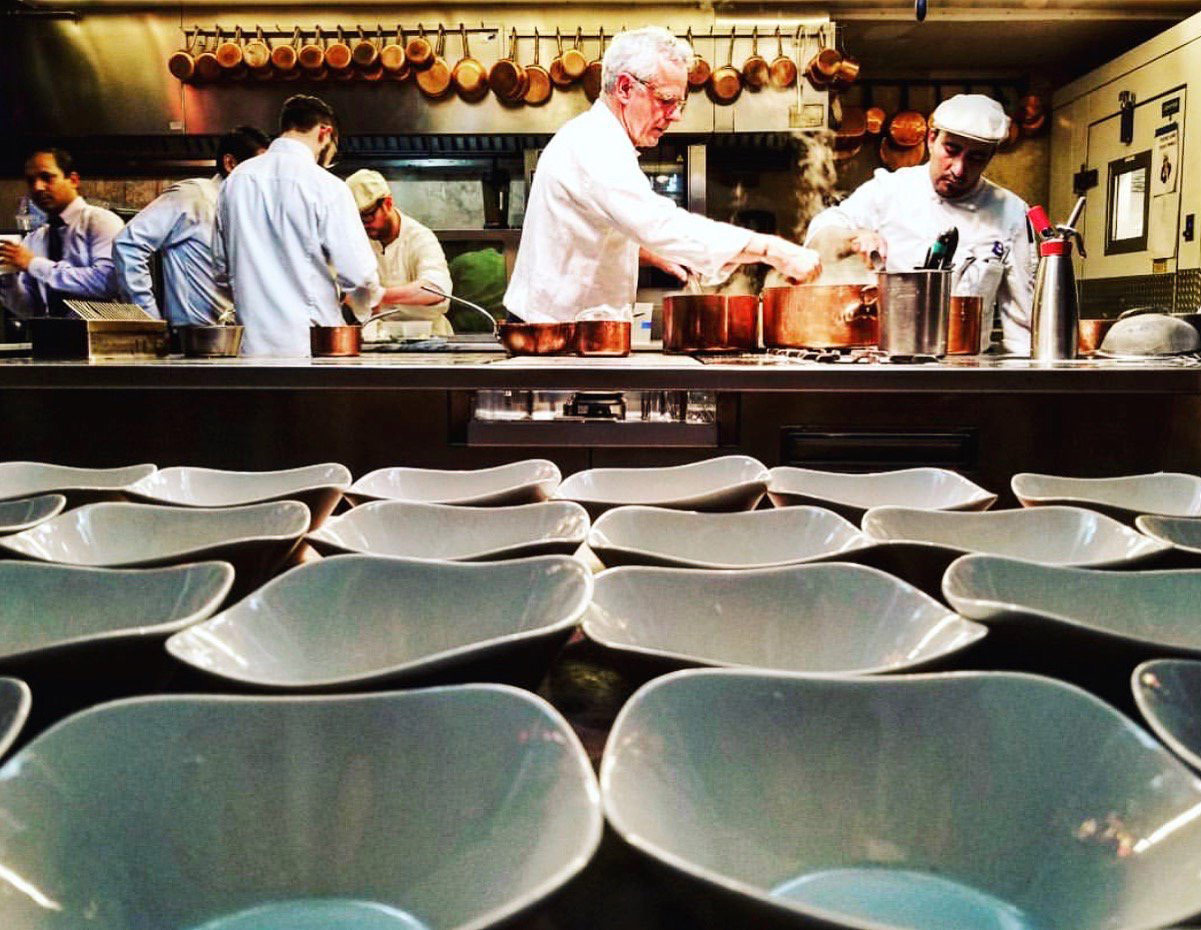 David Bouley is seasoning a sauce being cooked in copper pots, with busy team in background