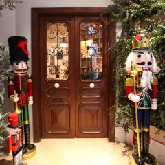 French Doors entrance to Bouley Test Kitchen Decorated for the Holidays trimmed with greenery and Life sized wooden toy Christmas Dolls.