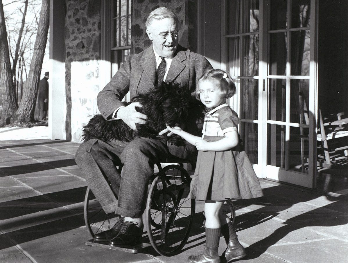 FDR in his wheel chair holding his dog in his lap