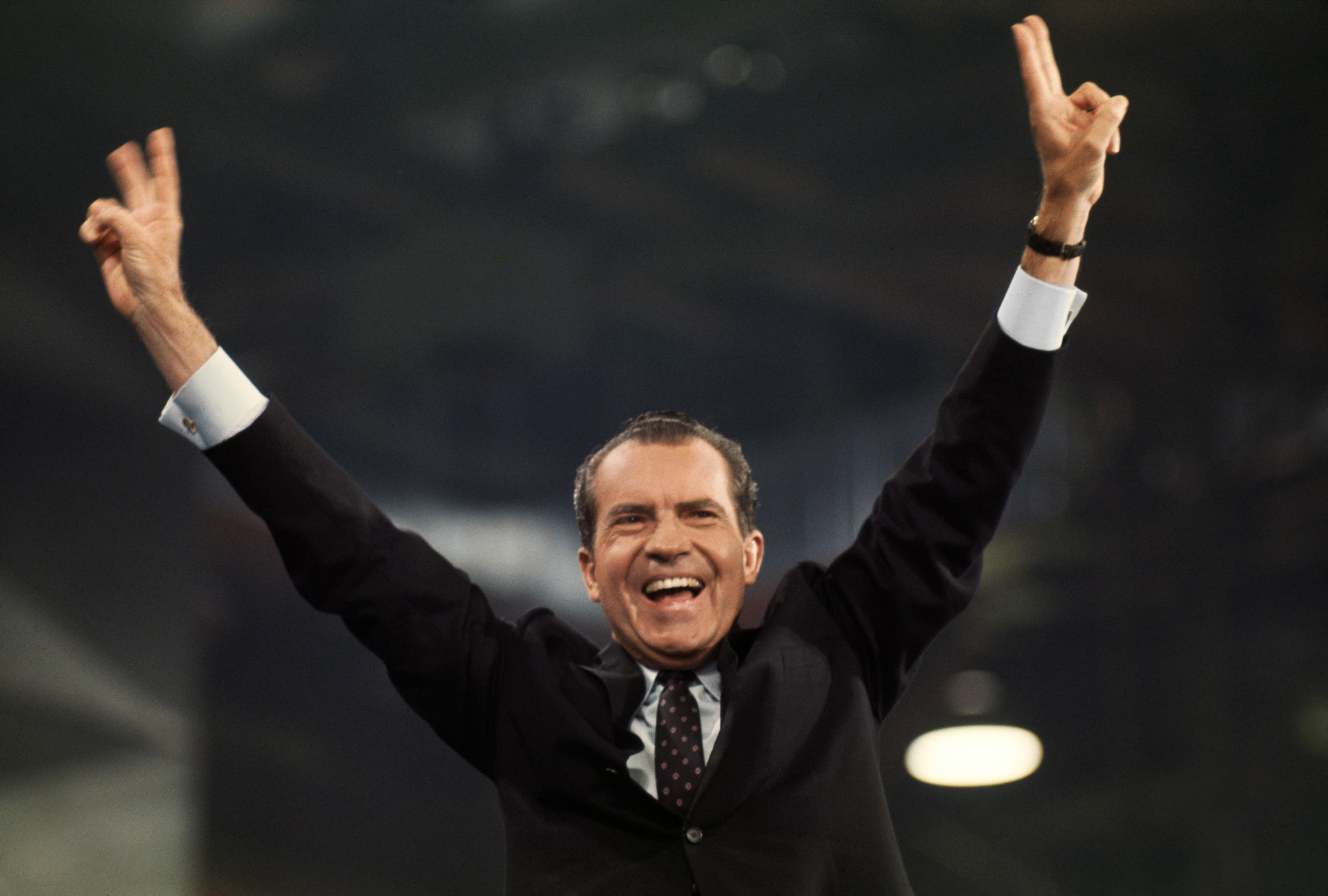 President Nixon raises both hands triumphantly overhead.