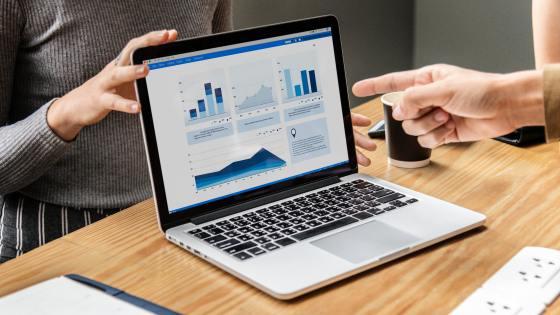 A laptop displays data analysis via graphs.