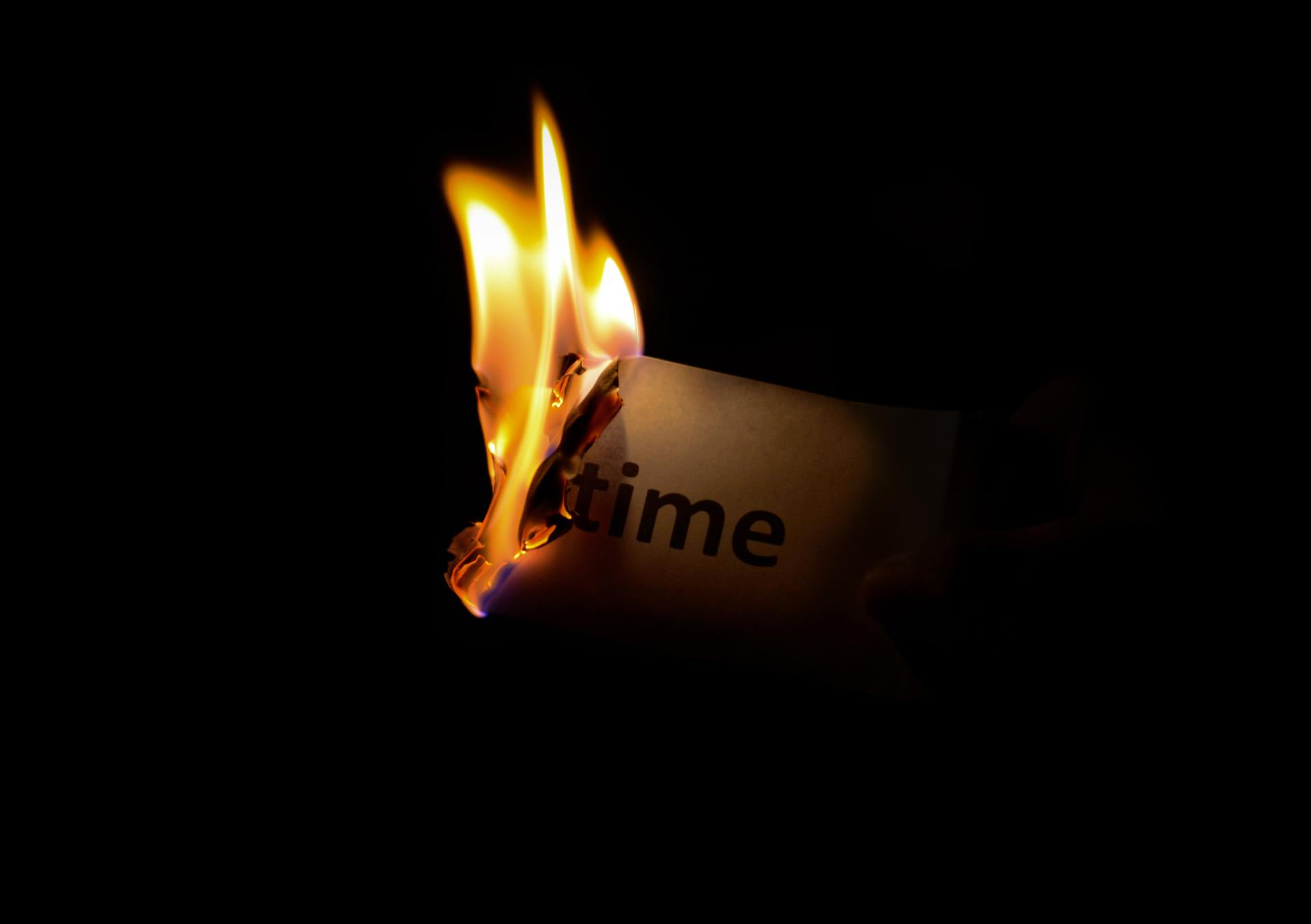 """A person holds a burning piece of paper that reads """"time""""."""