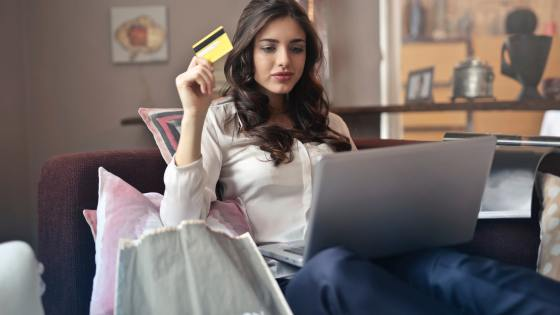 A young lady holds a credit card while sitting with a laptop on her lap.