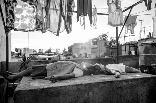 Image from the movie Roma by Alfonso Cuaron showing a woman and child lying below a line of laundry