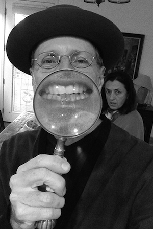 Photo of David Gilbert holding a magnifying glass in front of his mouth to enlarge his smile
