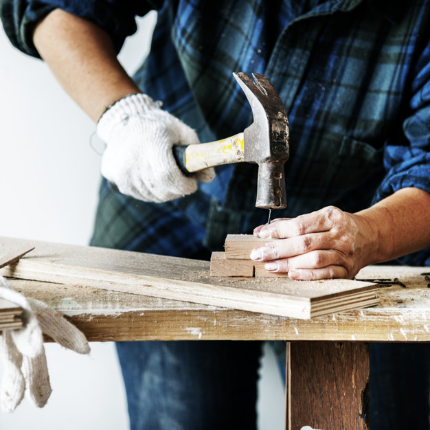 woman carpenter using hammer pushing nail on a wood 53876 70 - DIY vs. Hired: Pros and Cons of Each Construction Approach
