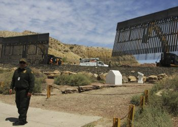 A US Border Patrol agent is seen next to workers building a border fence in a private property located in the limits of the US States of Texas and New Mexico taken from Ciudad Juarez, Chihuahua state on May 26, 2019. (Photo by HERIKA MARTÍNEZ / AFP)