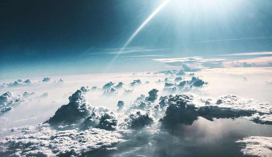 blissful view from a plane looking down on clouds bathed in sunlight