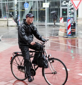 A man cycling in the rain in Utrecht, Netherlands.
