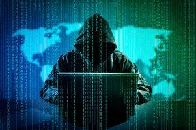Man on laptop hacking computer.
