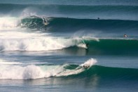 Photo of David Sills - Surfer-Saxophonist riding a wave at Bali Impossibles as two other surfers ride other waves.