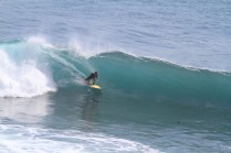 Photo of David Sills - Surfer-Saxophonist crouching low riding a wave left with right hand on board and skimming wall of water with his left hand
