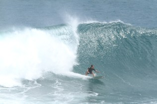 Photo of David Sills - Surfer-Saxophonist sliding left easily outpacing a large cresting wave