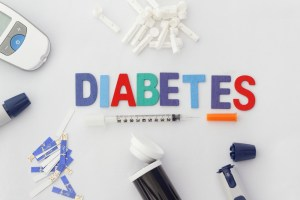 Word DIABETES with insulin syringe,lancet,test strip,glucose meter and lancing device on isolated white background