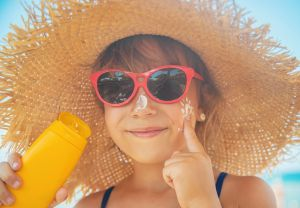 Little girl with hat sunglasses and sunscreen