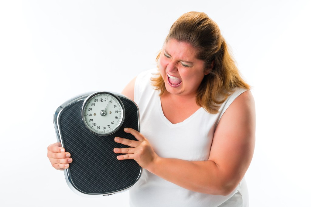 Obese woman angry with scale