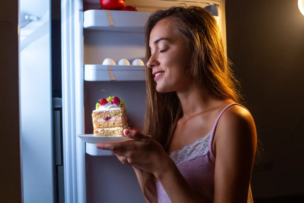 woman eating cake in front of open refrigerator