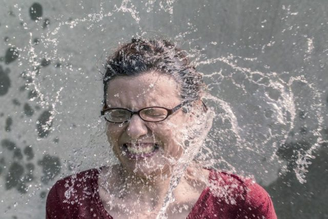 Woman using cold water to keep cool