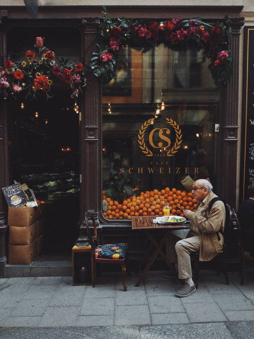 man in brown jacket sitting on chair in front of fruit stand