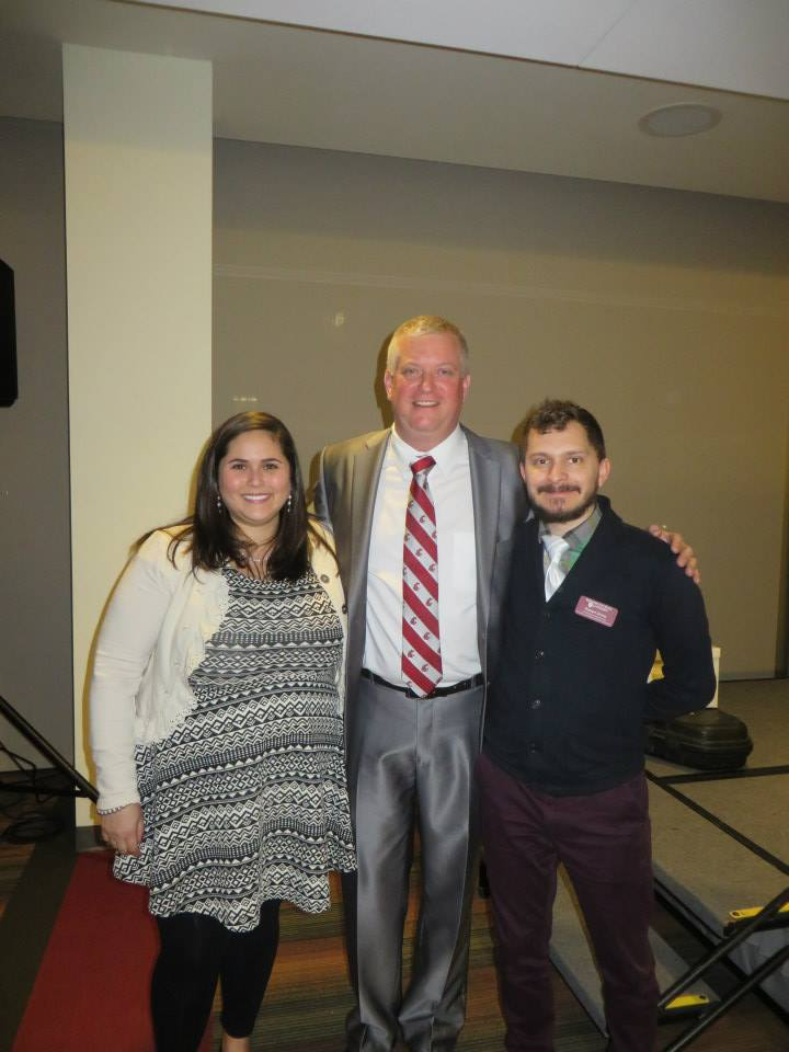 Photo of Davi with her colleague Robbie Zinna standing next to the Speaker of the Wiley Research Expo.