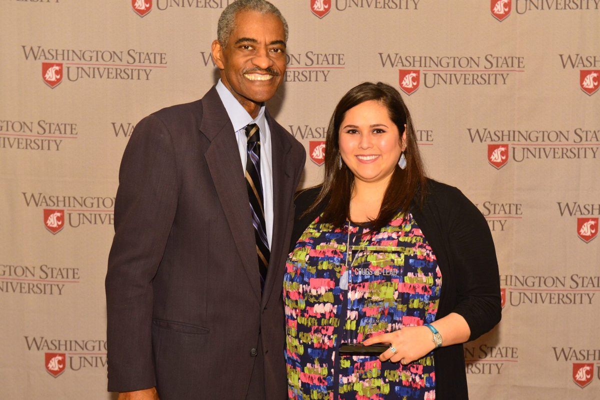 Photo of Davi and the late WSU President Elson Floyd. They are both smiling at the camera in front of a WSU background. Davi is holding up a trophy.