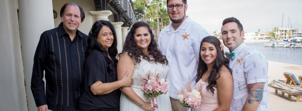 Photo of Davi on her wedding day. She is surrounded by her mom, dad, sister in law, brother and husband. They are all smiling and looking at the camera.