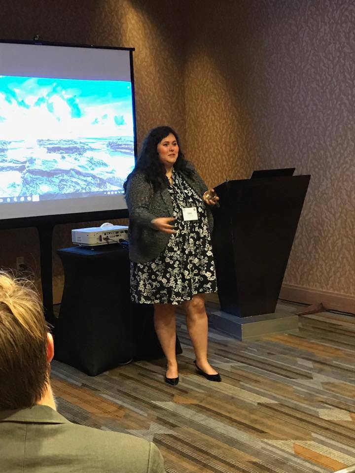 Photo of Davi in a dress standing in front of an audience presenting.