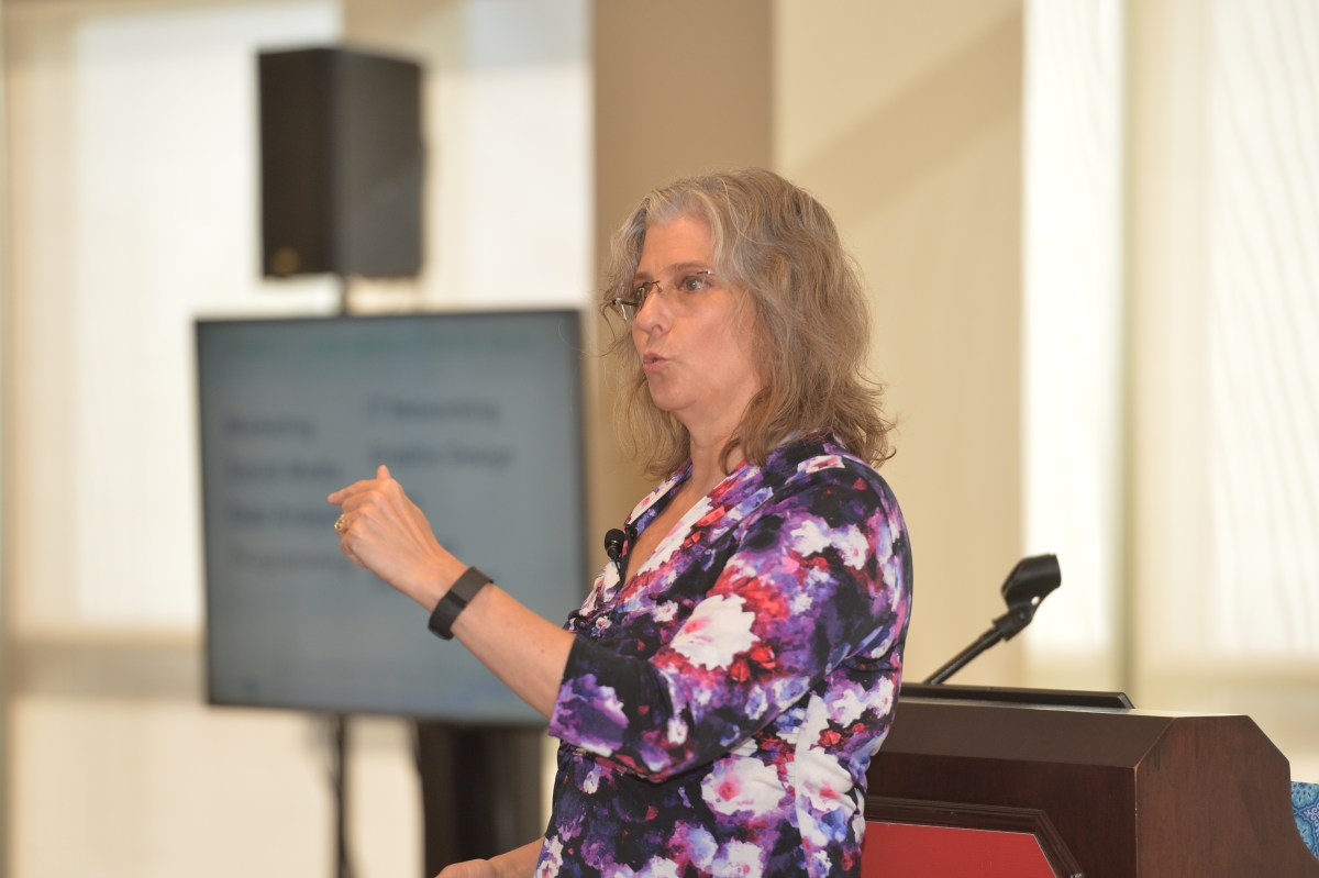 Photo of Paula Chambers talking to the audience with her hand up.