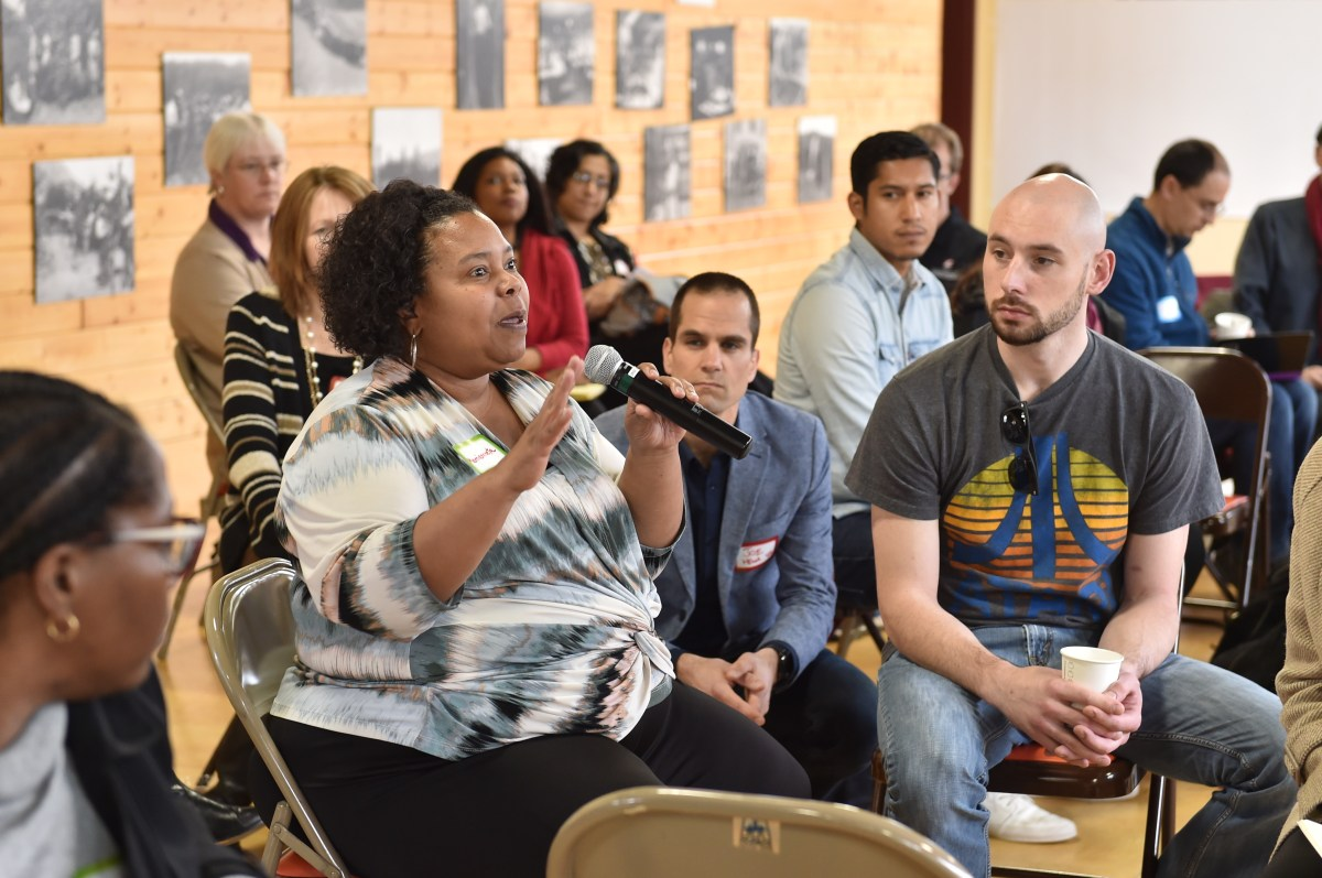 Photo of Liberating Structures WSU cohort from 2016. Audience member has the camera and is asking a question