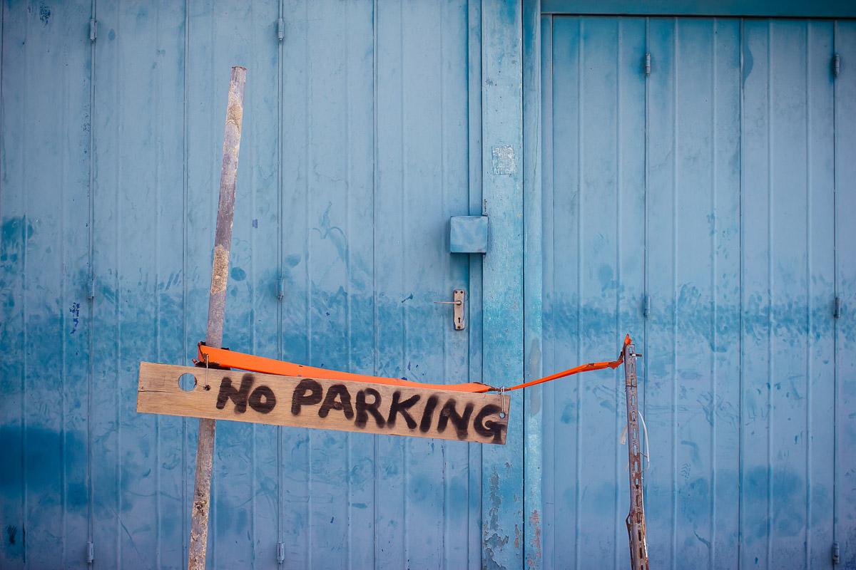 Handgeschriebenes hölzernes Parkverbotsschild vor blauer Garagentür