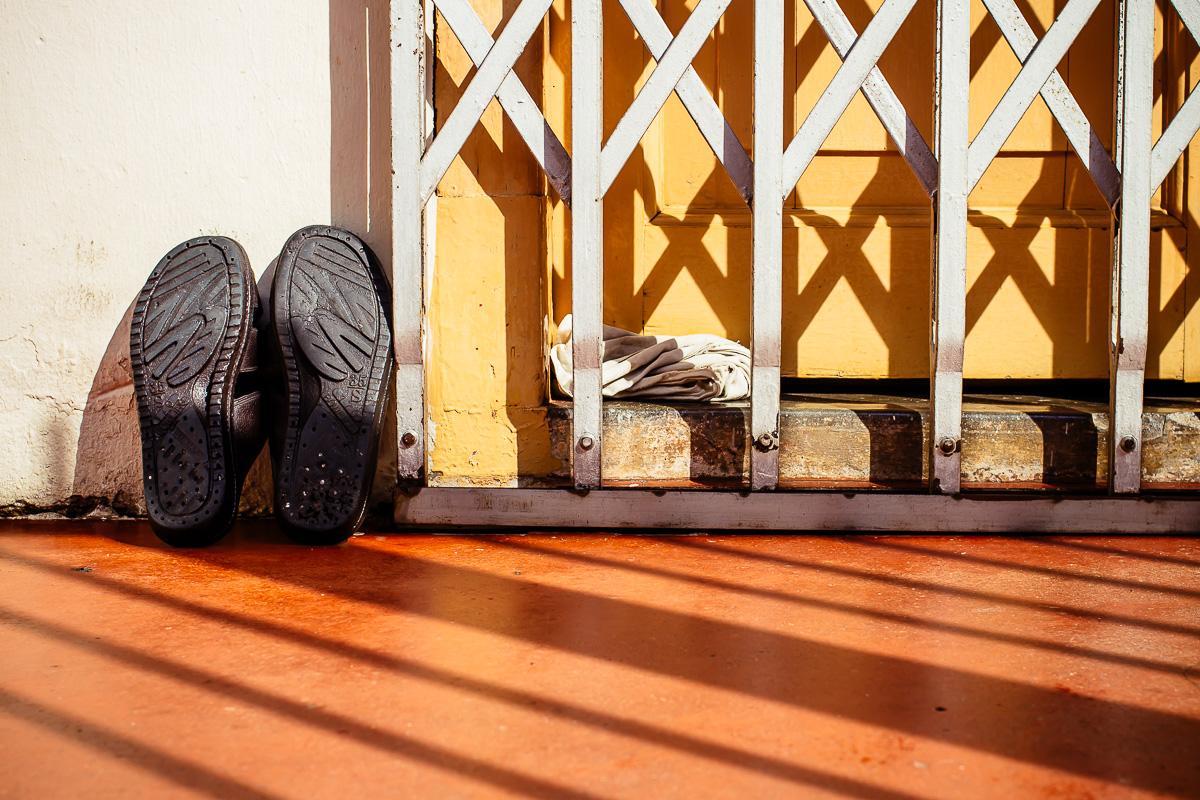 Black shoes on orange ground next to yellow door with metal grid
