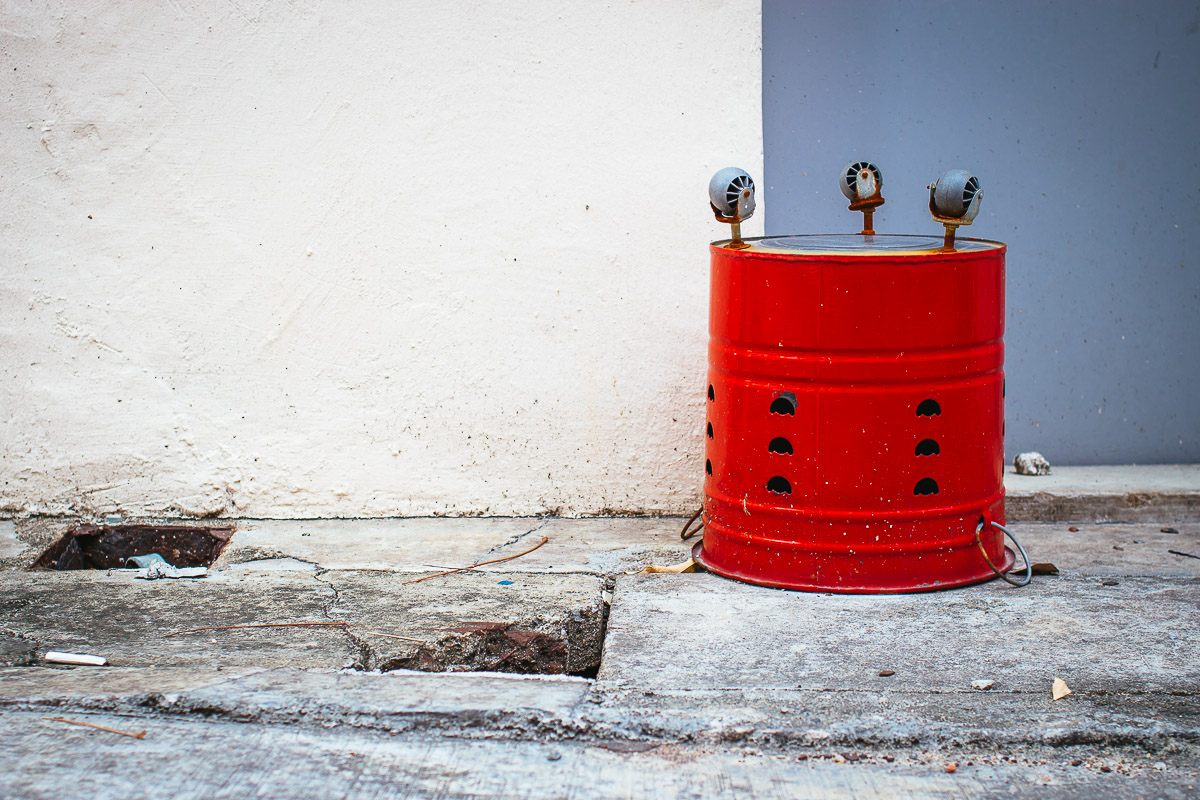 red bucket with wheels upside down in front of white and grey wall